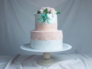 A beautiful spring two-tiered cake decorated with roses from mastic top and ornament around. Concept confectionery floristics. Food design. trends