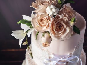 Beautiful three-tiered wedding cake in the form of dresses with lace and ribbon in a corset decorated with flowers and roses on top. The concept of unusual wedding desserts