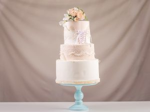 A large tiered wedding cake in the form of dress with lace decorated with pink roses on top of the table. The concept of festive desserts