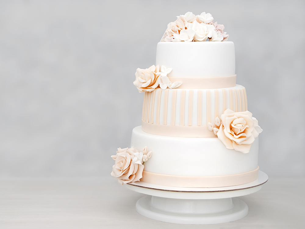 Three-tiered white wedding cake decorated with flowers from mast