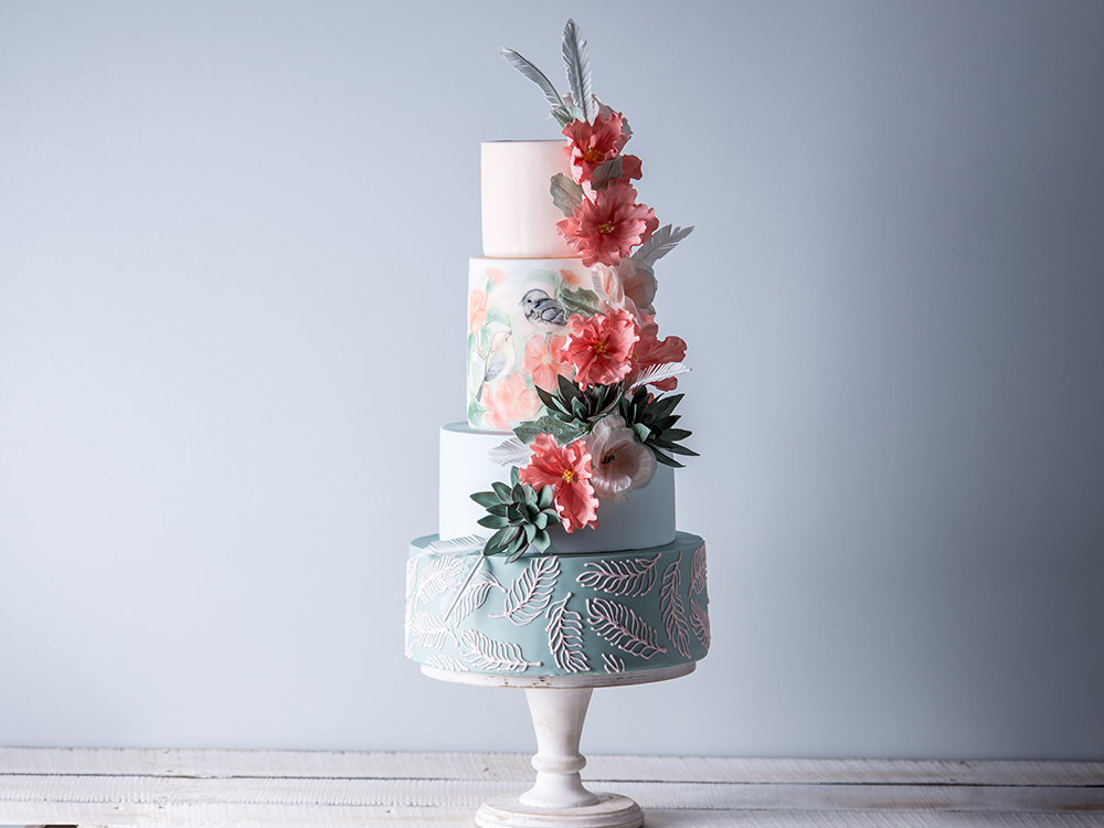 Beautiful home wedding four-tiered cake decorated with spring red flowers and handmade pattern. The concept of delicious desserts