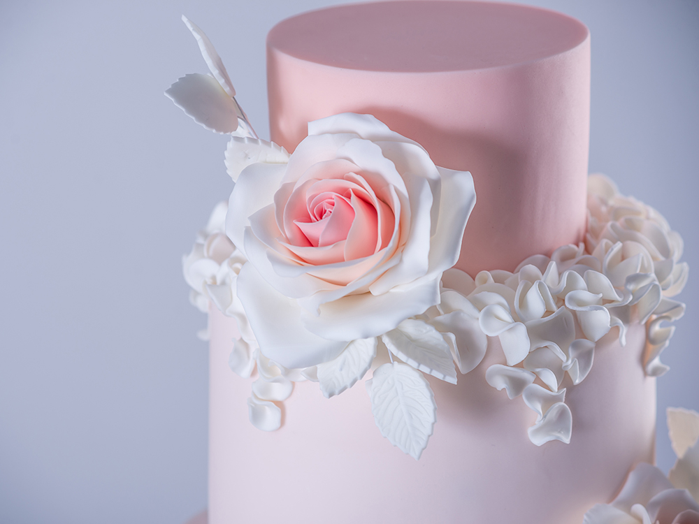 Beautiful elegant four tiered pink wedding cake decorated with roses flowers. The concept patisserie floral from sugar mastic